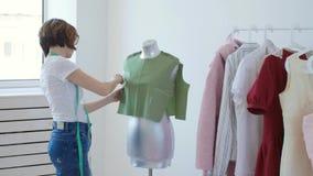 Hobby e piccola impresa Giovane sarto femminile che lavora con il tessuto del panno in officina archivi video