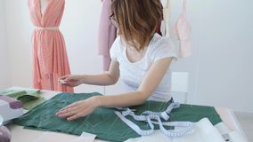 Hobby e piccola impresa Giovane sarto femminile che lavora con il tessuto del panno in officina stock footage