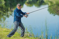 Hobby fisherman is trying to take his catch out of the water. Royalty Free Stock Photography