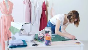 Hobby i mały biznes M?ody kobieta krawczyna pracuje z sukienn? tkanin? w warsztacie zbiory