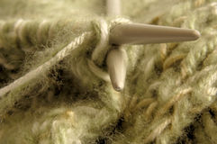 Hobby knitting,Two knitting needles with green wool Royalty Free Stock Image