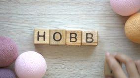 Hobby kvinna som gör ord av träkuber, färgrika trådbollar som ligger på tabellen lager videofilmer