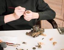 Hobby- och fritidbegrepp Tonårig pojke som monterar och målar plas arkivbild
