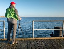 Hobby photograph with camera on tripod in hand. Wooden board  bridge. Hobby photograph with camera on tripod in hand. Wooden board quay, sunny morning at sea Royalty Free Stock Photography