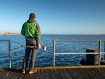 Hobby photograph with camera on tripod in hand. Wooden board  bridge. Hobby photograph with camera on tripod in hand. Wooden board quay, sunny morning at sea Stock Photos