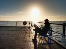 Hobby photograph sit on bench at camera on tripod. Wooden board quay Stock Photo