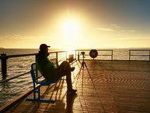 Hobby photograph sit on bench at camera on tripod. Wooden board quay Royalty Free Stock Photo