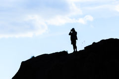 Hobby photographer. Black silhouette of hobby photographer or common tourist with camera capturing the view from the top of the hill Royalty Free Stock Image