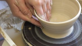 Hobby pottery master class workshop forming clay. Handmade hobby pottery courses. master class at workshop. potter forming clay bowl on turning wheel stock video footage