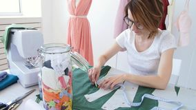 Hobby and small business. Young female tailor working with cloth fabric in workshop stock footage