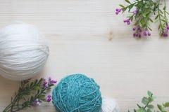 hobby sticka garn för många folk Garnnystan och blommor på en träbakgrund Garn för handarbete Lekmanna- lägenhet, kopieringsutrym arkivfoton