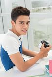 Hobby. Vertical portrait of a college student holding a modern photographic camera Royalty Free Stock Photo
