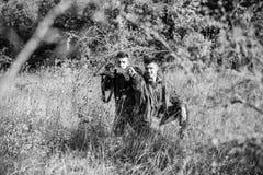 Hobby voor echt mensenconcept Jagers met geweren in aardmilieu Jagersjachtopzieners die dier of vogel zoeken stock afbeelding