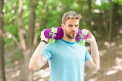 Hobbybegrepp Mannen som ler framsidan som poserar med encentmyntbrädet, parkerar naturbakgrund som är defocused Grabben bär på en Royaltyfria Foton