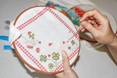 Hobbyhus Hand-gjorda produkter Flickan broderar nära övre för bild Händer, visare, tråd och broderi arkivbild
