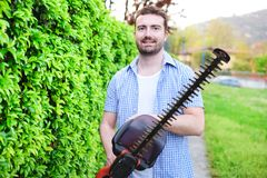 Hobbyist gardener using an hedge clipper in the home garden. Hobbyist gardener using an hedge clipper in his home garden royalty free stock photography
