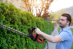 Hobbyist gardner using an hedge clipper in the home garden. Hobbyist gardner using an hedge clipper in his home garden stock image