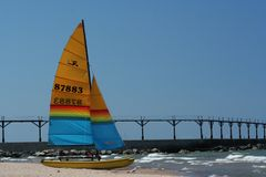 Catamaran sitting on the beach on Lake Michigan in Michigan City, Indiana. Hobie Cat catamaran sitting on Washington Park Beach on Lake Michigan in Michigan City royalty free stock images