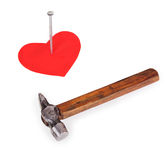 Hobnail in a red heart and a hammer Stock Photos