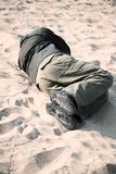 Hobo. Homeless man sleeping on sand, selective focus on nearest part of man stock image