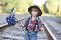 Hobo. Adorable little girl dressed as a hobo and walking on the railroad tracks. Room for your text royalty free stock photo