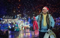 Hobo catches a taxi. Excited tramp with shopping bags catches a taxi. Hobo in Santa Claus hat was on Christmas sales. It is snowing. Blurred night holiday stock photos