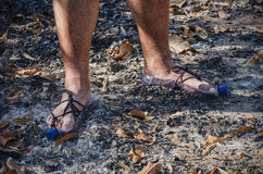 Hobo standing in bottle sandals on wood ashes. Hobo feet standing on wood ashes in homemade sandals from empty plastic bottles stock images