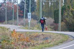 Hobo on a Winding Road. A hobo or vagabond carries his worldly belongings in a plastic bag as he walks a long and winding road stock photo