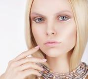 Hoch entwickelte reizende Blondine, die ihr Gesicht berührt Stockfoto