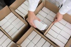Hoch-Winkelansicht von den Händen der Arbeitskraft verpackte Produkte in Ca einsetzend lizenzfreie stockfotos