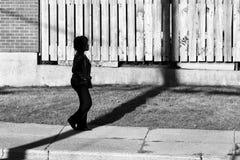 Hochauflösendes Schattenbild einer Frau, die auf einen Bürgersteig im Schatten geht Lizenzfreies Stockfoto