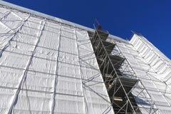 Hochbau, das Gebäude bedeckt mit einer grauen Plane Lizenzfreies Stockfoto