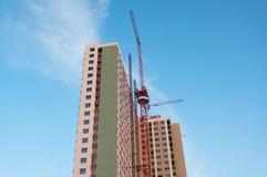 Hochbau mit rotem Kran im Hintergrund des blauen Himmels Stockbilder
