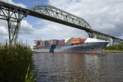 Hochdonn - Container vessel at the Kiel Canal under the railroad bridge Royalty Free Stock Photography