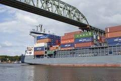 Hochdonn - Container vessel at the Kiel Canal under the railroad bridge Stock Photo