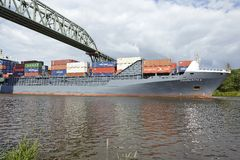 Hochdonn - Container vessel at the Kiel Canal under the railroad bridge Stock Photography