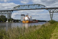 Hochdonn - Freighter at the Kiel Canal under the railroad bridge Royalty Free Stock Photo