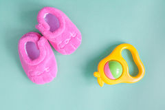 Hochet et butins de bébé sur le fond vert Photo stock