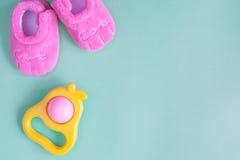 Hochet et butins de bébé sur le fond vert Photos stock