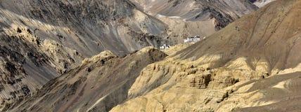 Hochgebirge des Lamayuru-Tales mit einem buddhistischen tibetanischen Kloster: weißes Klingelgebäude steht unter dem enormen Brau Stockbild