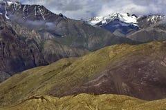 Hochgebirge: im frühen Plan eine gelbe Steigung, weitere braune Spitzen mit Schnee auf Spitzen, Himalaja Lizenzfreie Stockfotografie