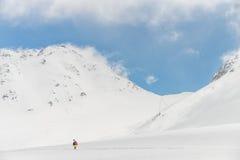 Hochgebirge unter Schnee mit klarem blauem Himmel und Hütte Stockbild