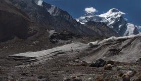 Hochgebirgegletscher: enorme Eisblöcke liegen auf den Steigungen der grauen Moraine unter den Hoch Schnee-mit einer Kappe bedeckt Stockbilder