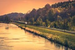 Hochgeschwindigkeitszug auf der Bank von einem Fluss im Abendsonnenuntergang Lizenzfreie Stockbilder