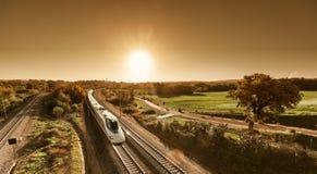 Hochgeschwindigkeitszug, der vom Sonnenaufgang sich nähert lizenzfreie stockbilder