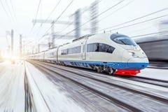 Hochgeschwindigkeitszug reitet an der hohen Geschwindigkeit im Winter um die schneebedeckte Landschaft stockfotos