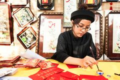 Young girl drawing calligraphy in Vietnam. HOCHIMINH CITY- VIETNAM: Young girl with traditional black costume drawing calligraphy ancient distich in Hochiminh royalty free stock photos