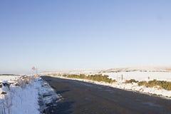 Hochlandlandstraße im Schnee mit Windpark stockbilder