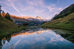 Hochroter Sonnenuntergang über Einbuchtung-Blanche Snowy-Berg, der in AR sich reflektiert stockbilder