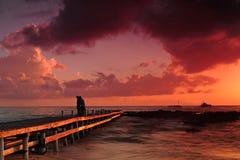 Hochroter Sonnenuntergang über Anlegestelle Stockbild